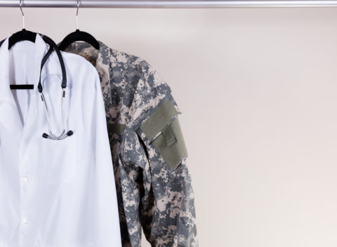 Medical Doctor Consultation white coat, stethoscope around collar, and military uniform hanging on rack. Off white wall in background. Horizontal layout with copy space.